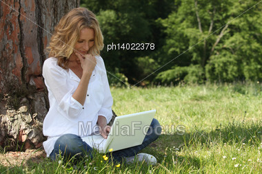 Blond Woman Sat By Tree With Laptop Stock Photo