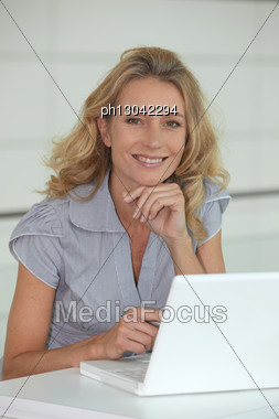 Blond Woman Sat At Desk With Laptop Computer Stock Photo