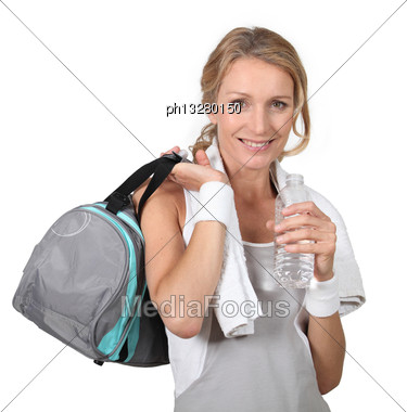 Blond Woman Wearing Sportswear Holding Water Bottle With Bag Over Shoulder Stock Photo