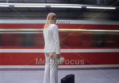 Blonde Business Woman Waiting As Train Speeds By Stock Photo