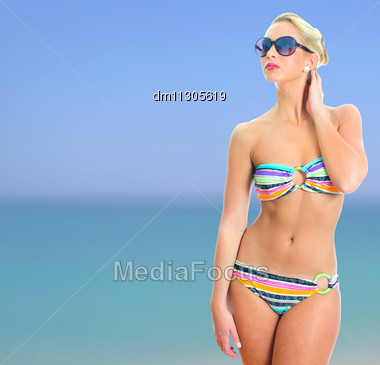 Blonde Girl In Striped Bikini And Sunglasses Over Sea Background Stock Photo