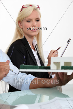 Blonde Woman Dressed In Suit And A Man Looking A House Scale Model Stock Photo