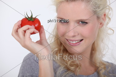 Blonde Woman Holding A Tomato In Her Hand Stock Photo
