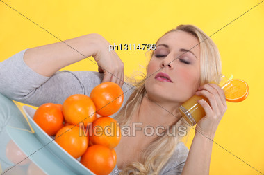 Blonde Woman Refreshing His Face With An Orange Juice Glass Stock Photo