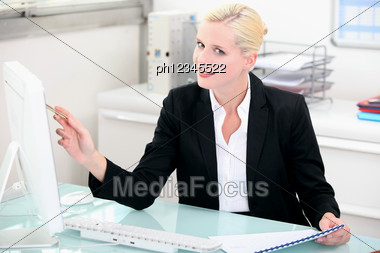 Blonde Woman Working At A Clean Modern Desk Stock Photo