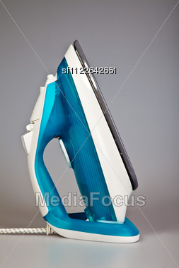 Blue Electric Iron Isolated On Grey Background Stock Photo