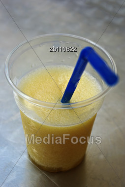 Blue Straw In Yellow Ice Cold Beverage In Plastic Glass On Table Stock Photo