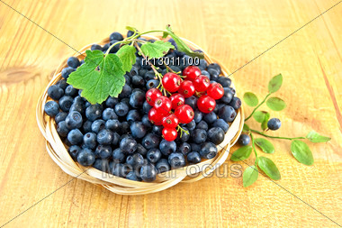 Blueberries With Sprigs Of Red Currants In A Wicker Basket, A Sprig Of Blueberries With Green Leaves On A Wooden Board Stock Photo