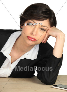 Bored Employee Leaning On Her Desk Stock Photo