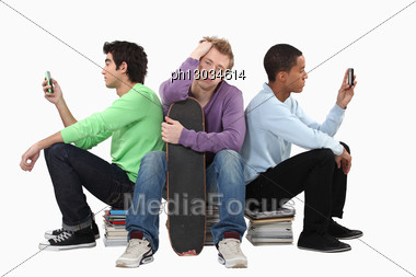 Bored Teenagers Sat On Piles Of Books Stock Photo