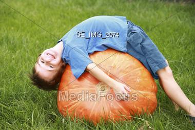 Boy Bending over on Pumpkin Stock Photo