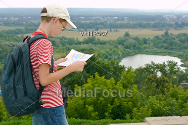 Boy with binoculars and backpack looks at the map on a hike Stock Photo