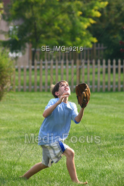 Boy Catching Baseball Stock Photo