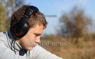 Boy Enjoying Music In Headphones In Autumn Day Stock Photo