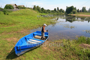 Boy Fishes On Coast River Stock Photo
