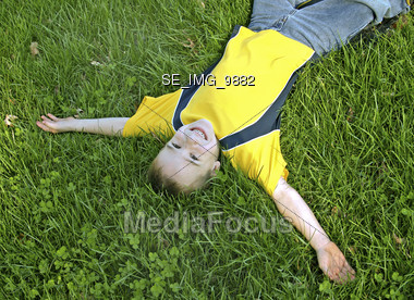 Boy Laying in Grass with Arms Outstretched Stock Photo