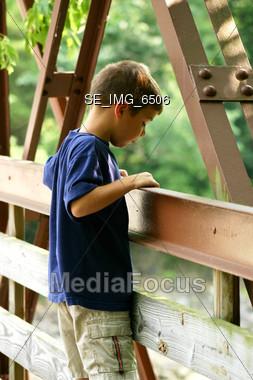 Boy Looking Over Bridge Stock Photo