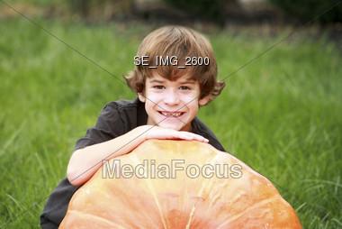 Boy on Large Pumpkin Stock Photo