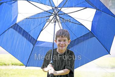 Boy Under Umbrella in the Rain Stock Photo