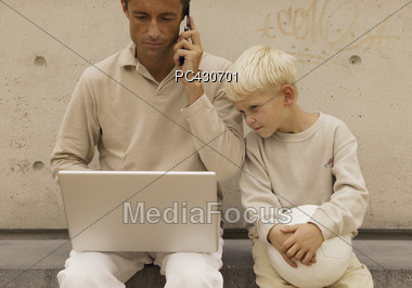 Boy Watching Dad Working On Laptop Outside Stock Photo