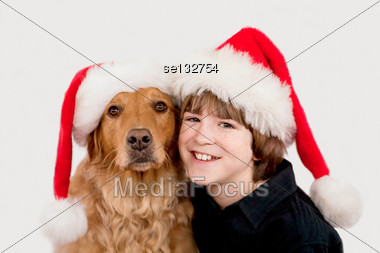 Boy With Dog in Santa Hats Stock Photo