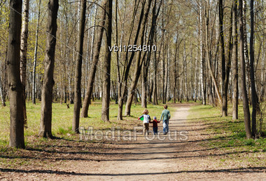 Boy With The Sisters Walk In The Park Stock Photo