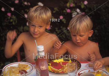 Boys Eating At A Picnic Stock Photo