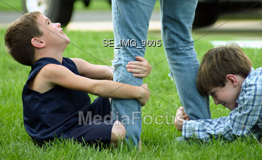 Boys Pulling on Persons Legs Stock Photo