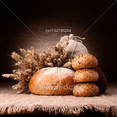 Bread, Flour Sack And Ears Bunch Still Life On Rustic Background Stock Photo