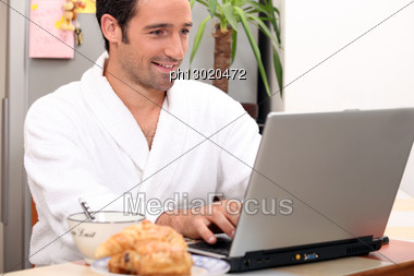 Breakfast In Bathrobe With Computer Stock Photo