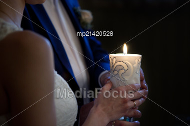 Bride And Groom Holding A Candle In Church Stock Photo