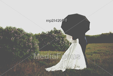 Bride And Groom Under Black Umbrella At Park Stock Photo