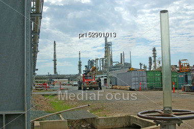BRISBANE, AUSTRALIA, SEPTEMBER 28, 2008: An Unidentified Worker Loads Pipes The BP Oil Refinery Near The Mouth Of The Brisbane River, September 28, 2008, Brisbane, Australia Stock Photo