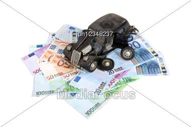 Broken Retro Car Model Laying Over Banknotes Stock Photo