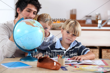 Brother And Sister Doing Geography Homework Stock Photo