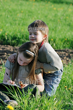 Brother And Sister Enjoy Summer Time In The Green Grass Stock Photo