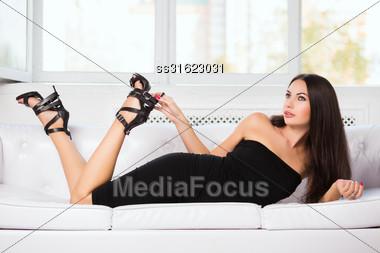 Brunette In Black Fitting Dress Posing On The Sofa Stock Photo