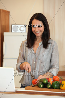 Brunette Chopping Vegetables In The Kitchen Stock Photo