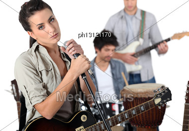 Brunette Singer With Guitar And Microphone And Male Musicians In Background Stock Photo