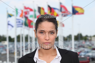 Brunette Stood In Front Of Flags Stock Photo