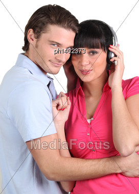 Brunette With Earphones And Boyfriend Cuddling Stock Photo