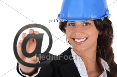 Brunette Woman In Blue Hard Hat Holding At Symbol Stock Photo