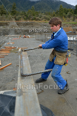 Builder Bends Reinforcing Steel For Foundations Work On A Large Construction Project Stock Photo