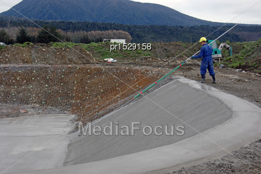 Builder Brushes Down Fresh Concrete In A Dairy Effluent Pond, Westland, New Zealand Stock Photo