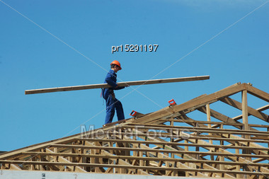 Builder Carrying Timber For The Roof Framing Stock Photo