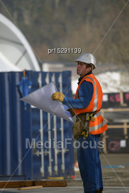 Builder Consults His Plans At The Construction Site Stock Photo
