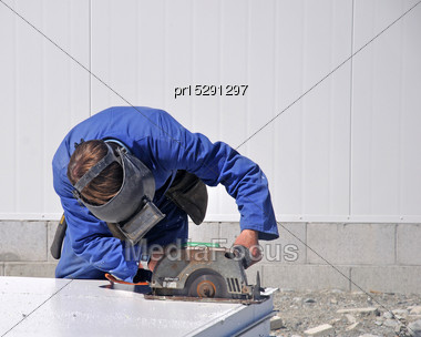 Builder Cuts A Sheet Of Isowall (polystyrene Sandwiched Between Sheet Metal) For The Walls Of A New Dairy, Westland, New Zealand Stock Photo