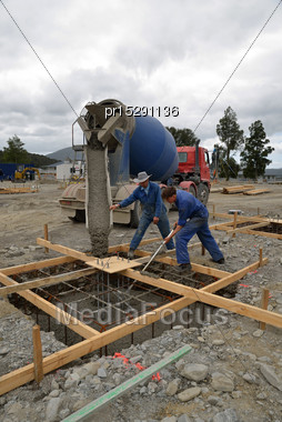 Builder Directing Wet Concrete Into Foundations Of A Large Building Stock Photo