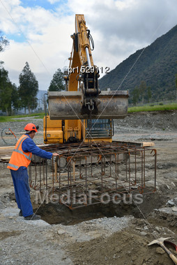 Builder Directs A Cage Of Reinforcing Rods Into The Foundation For A Portal A Large Building Stock Photo