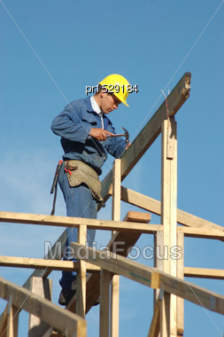Builder Driving Home A Nail While Finishing The Roof Framing Stock Photo